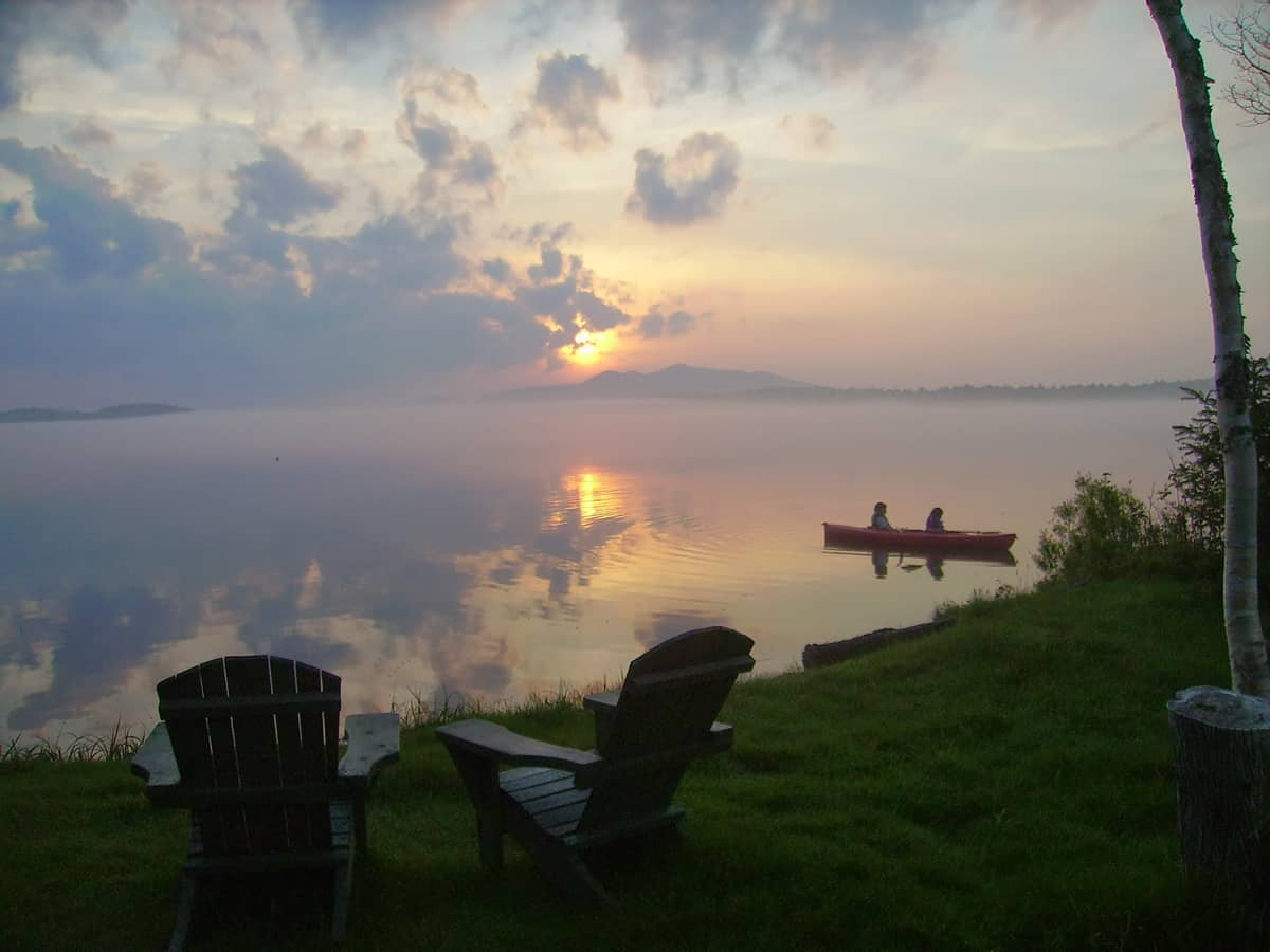 The sun rests on St. Regis Mountain across Lake Clear while beautiful fog roles in over the Lake Clear Lodge's private beach front. Two guests take a quiet paddle in a red double kayak.