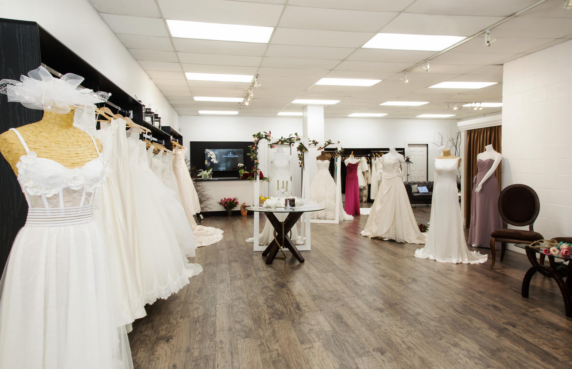 Picture of the interior of the Alma Bridal store showing a wide variety of custom wedding dresses and evening gowns.