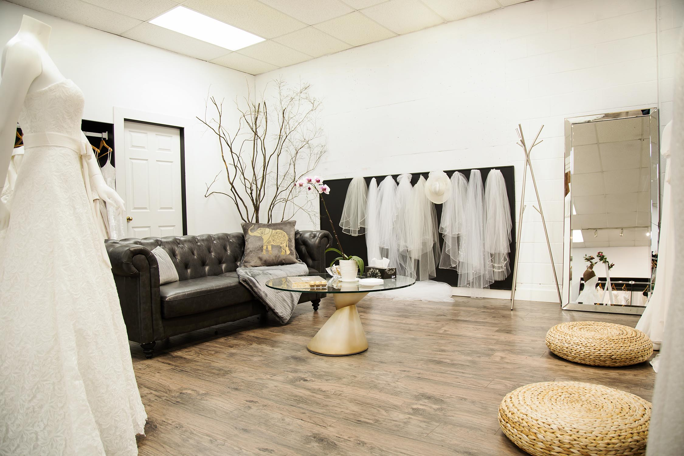 A picture of the fitting area in Alma Bridal. There is a sofa where other guests can sit and a large mirror for the brides to see themselves in.