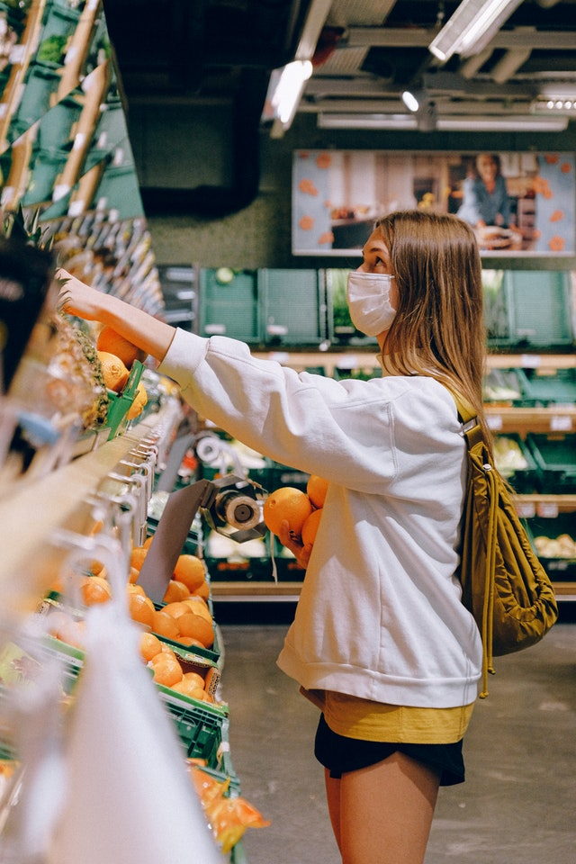 Woman shopping for groceries with face mask on
