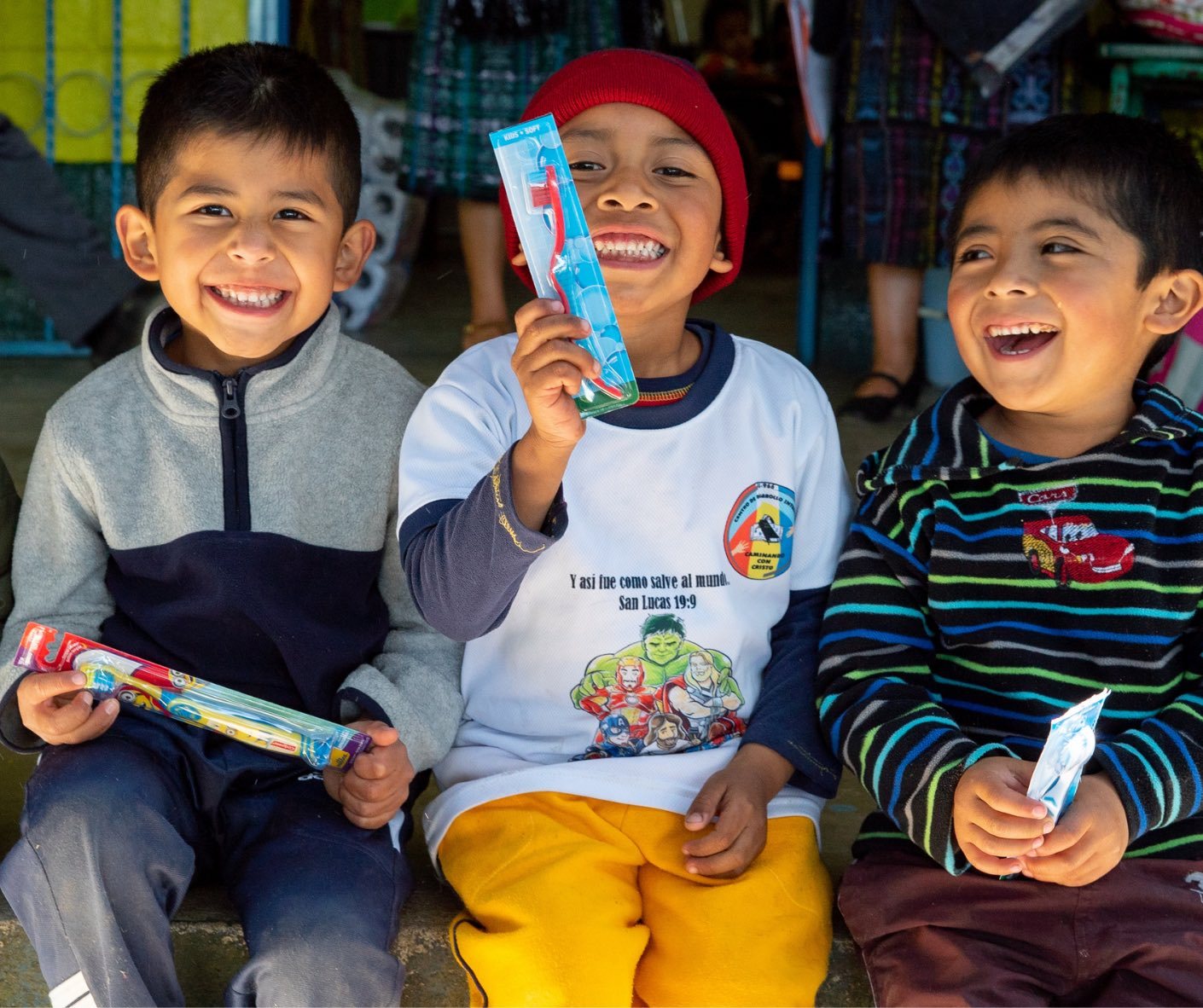 Children happy smiling holding up toothbrushes