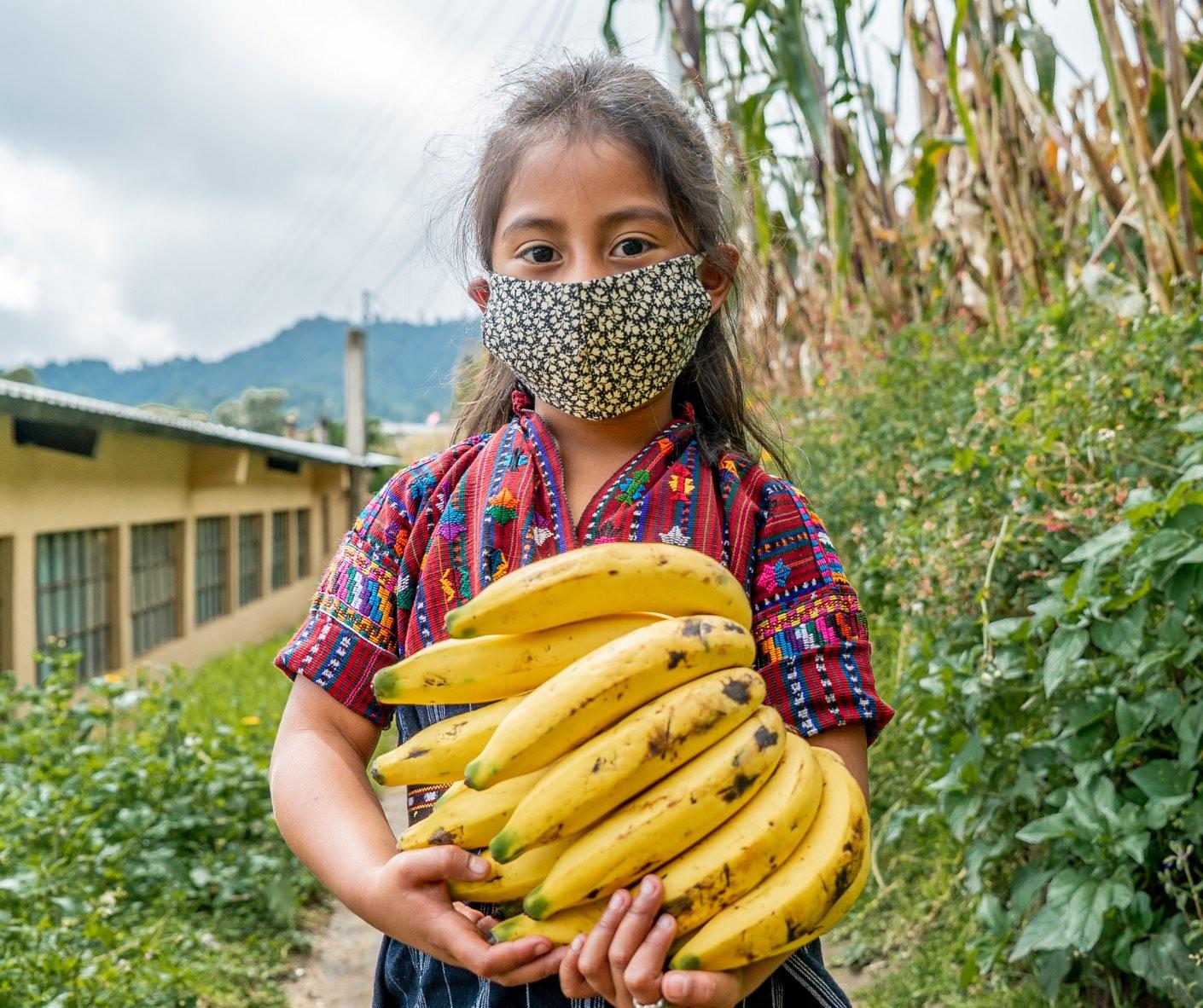 Guatemalan girl in mask holding bananas