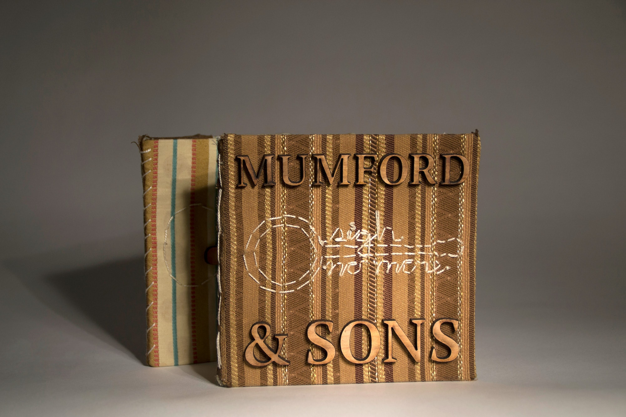 "The front cover of a fabric CD case. The artist name, Mumford & Sons, is cut from wood. The album name, ""Sigh no more"" is stitched on."