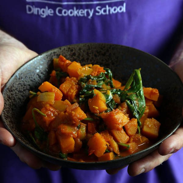 Person holding a bowl of local food in an apron with Dingle Cookery School written on it - one of the delicious things to do in Dingle town Ireland