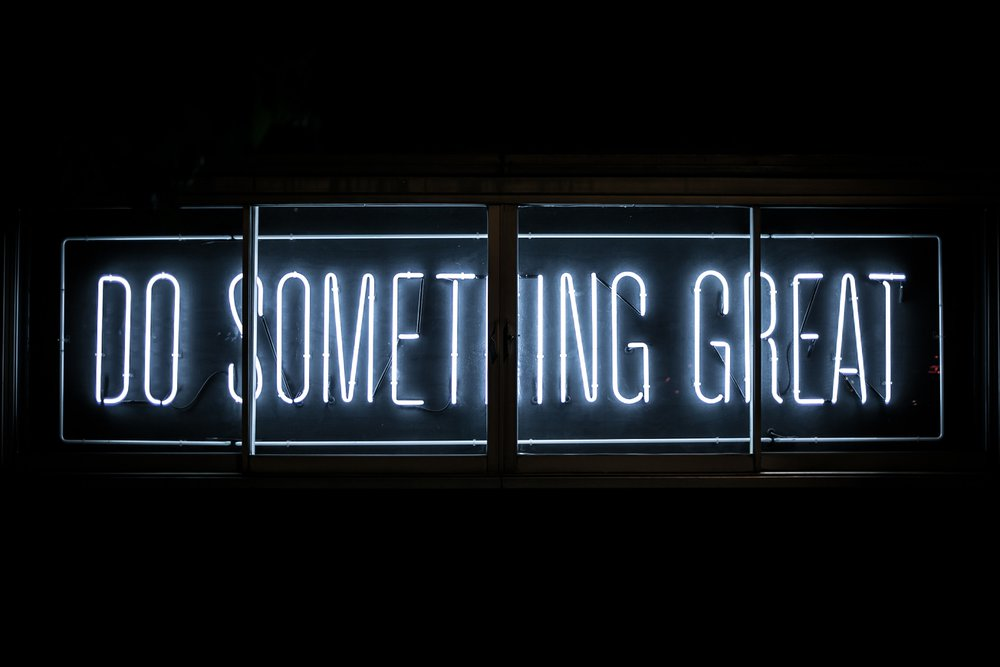 "A neon sign against a black screen that says ""Do Something Great"""