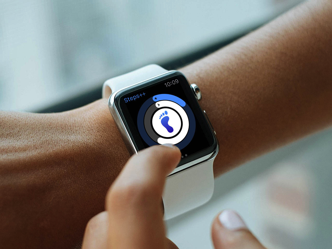 a raised hand showing an apple watch with the steps plus plus app shown on the watch's screen. the app is showing the progress of the wearer's step goals for the day.