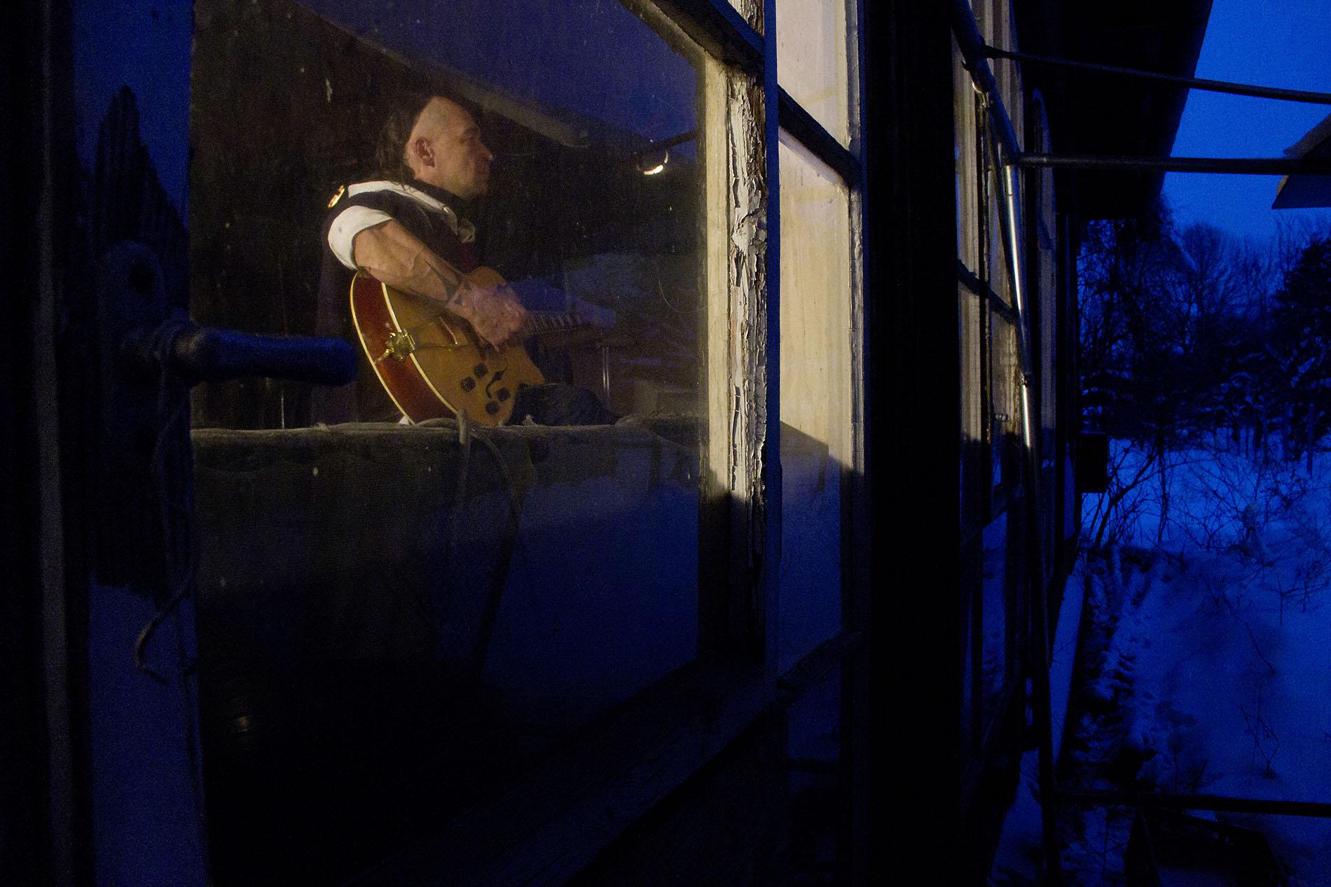 Sänger beim Gitarre spielen bis spät am Abend