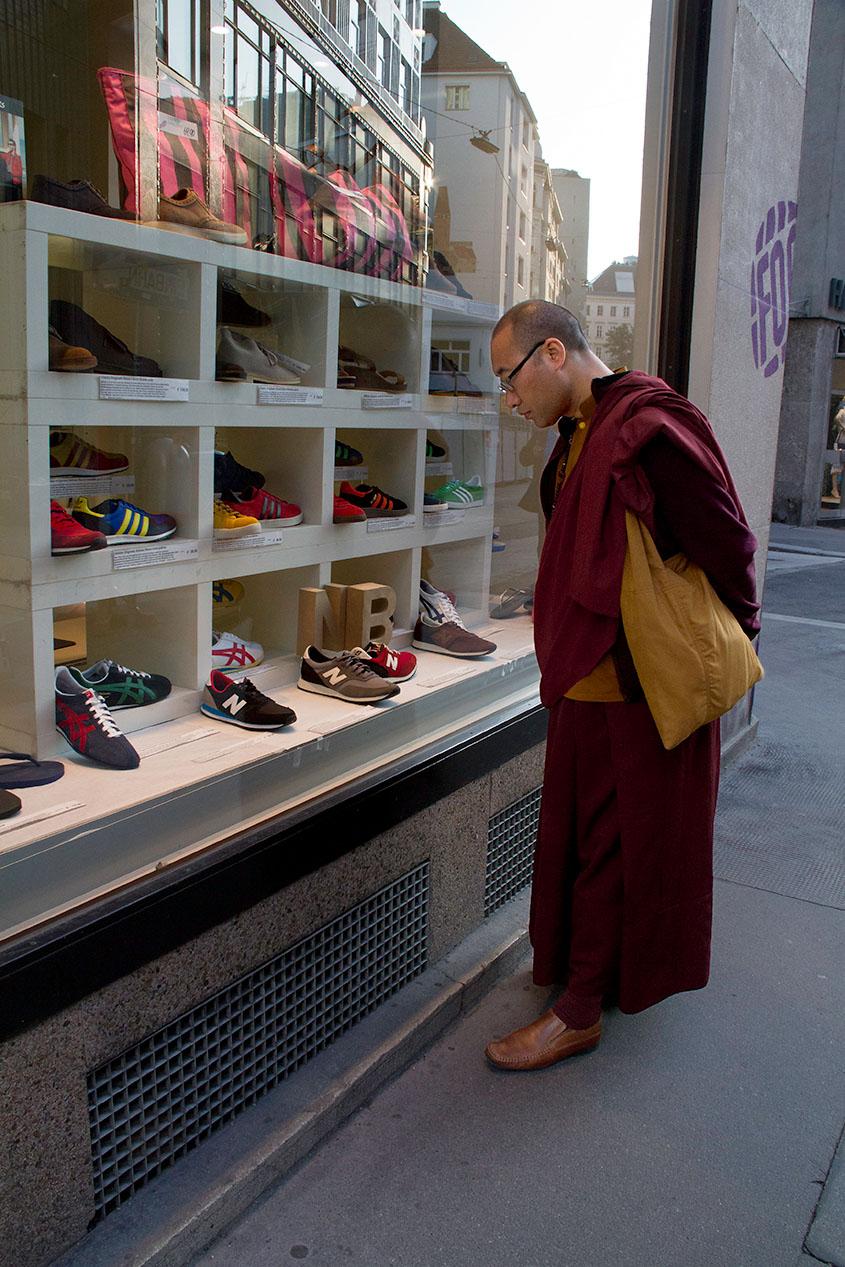 Mönch schaut neugierig in die Auslage eines Schuhgeschäftes