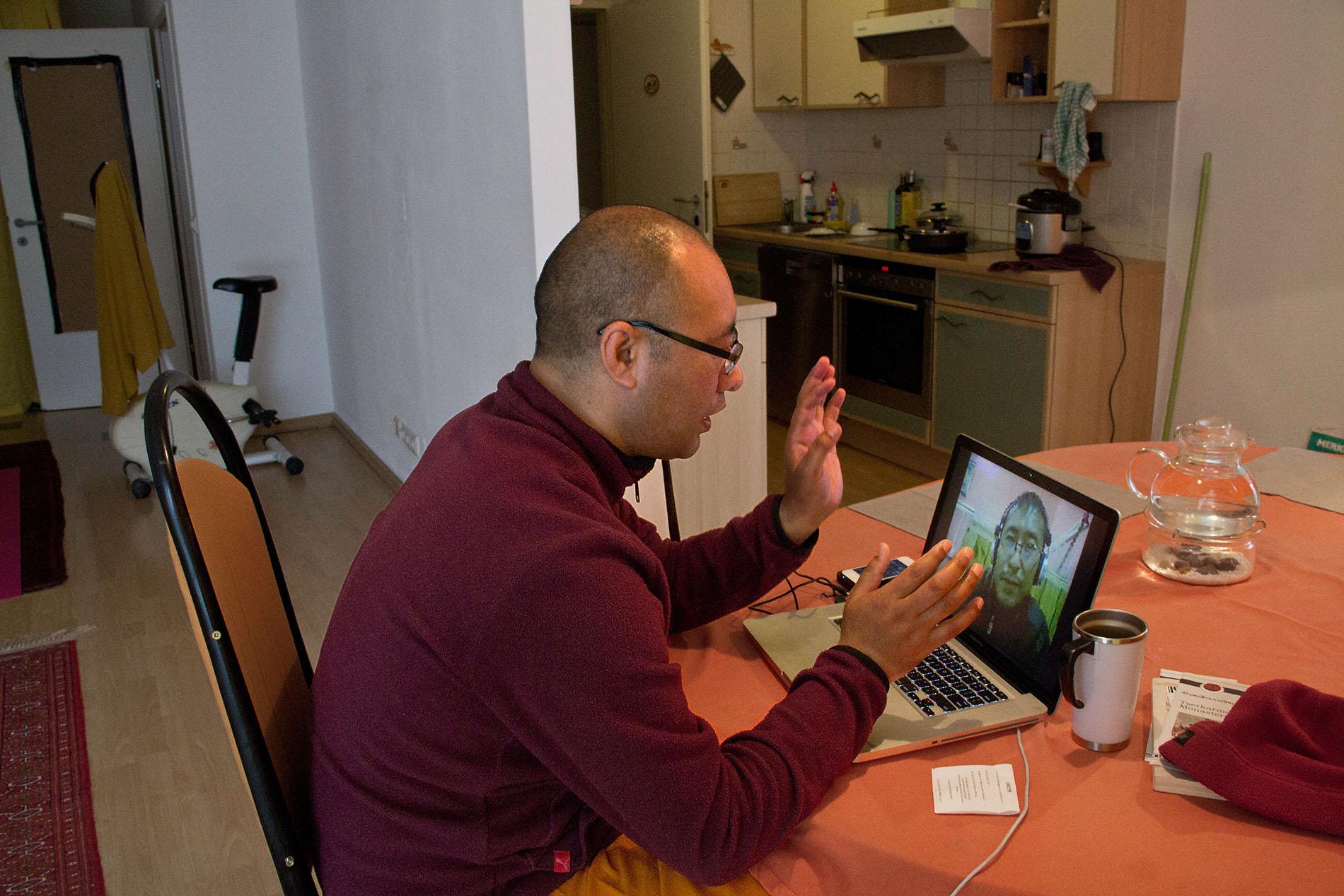 Mönch beim Skypen mit seinem Bruder in Indien