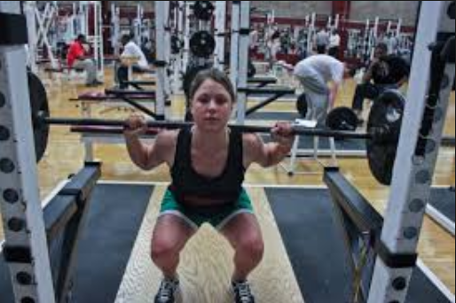 woman doing back squat in gym