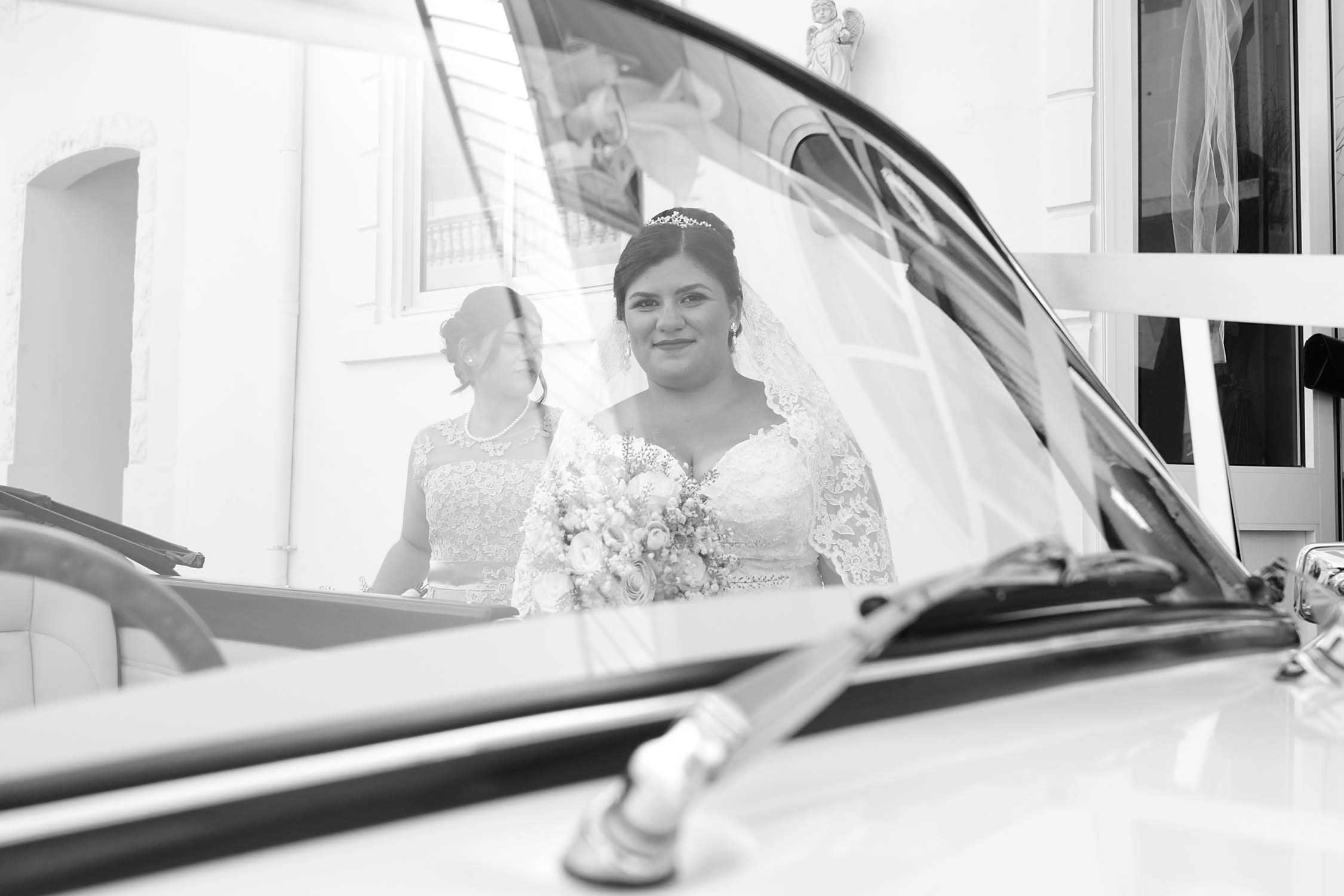 Bride Happily smiling before entering car to go to the wedding in Gozo