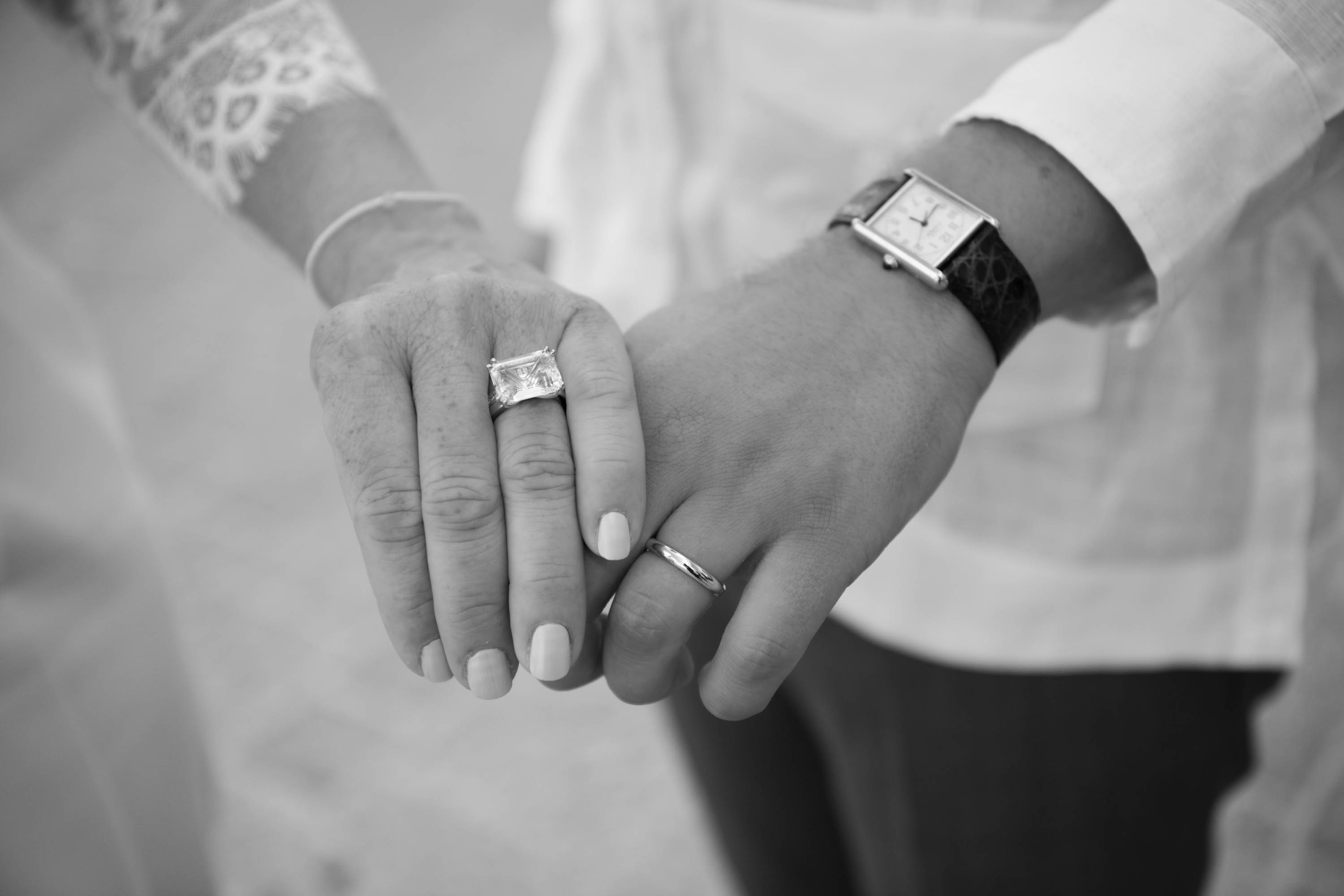Bride and Grooms hold hands showing off their wedding rings