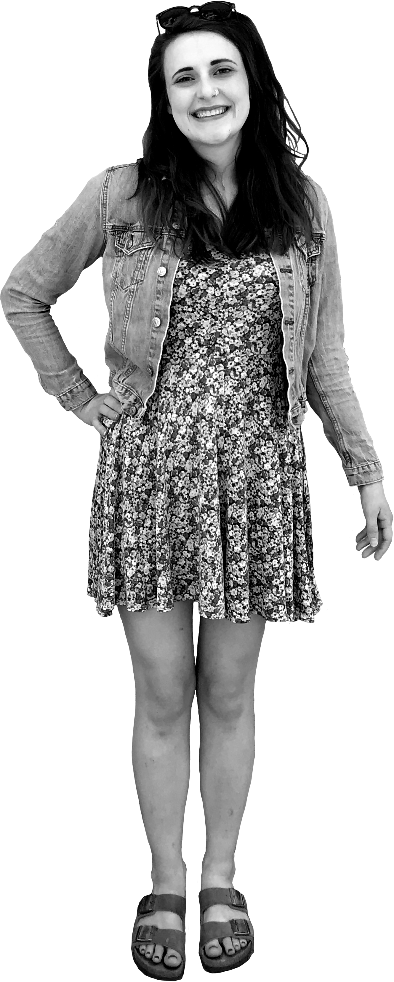 Image of Nicole standing with her right hand on her hip and her left arm extended. Nicole is white and has long, wavy dark brown hair. She is wearing a floral dress, jean jacket, birkenstocks, and has a pair of sunglasses on her head.