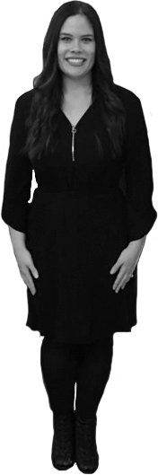 Image of Tiaonna standing with her arms tight to her sides, smiling at the camera. Tiaonna has long, smooth dark hair and a beautiful white smile. She is wearing a black dress with black tights and booties.