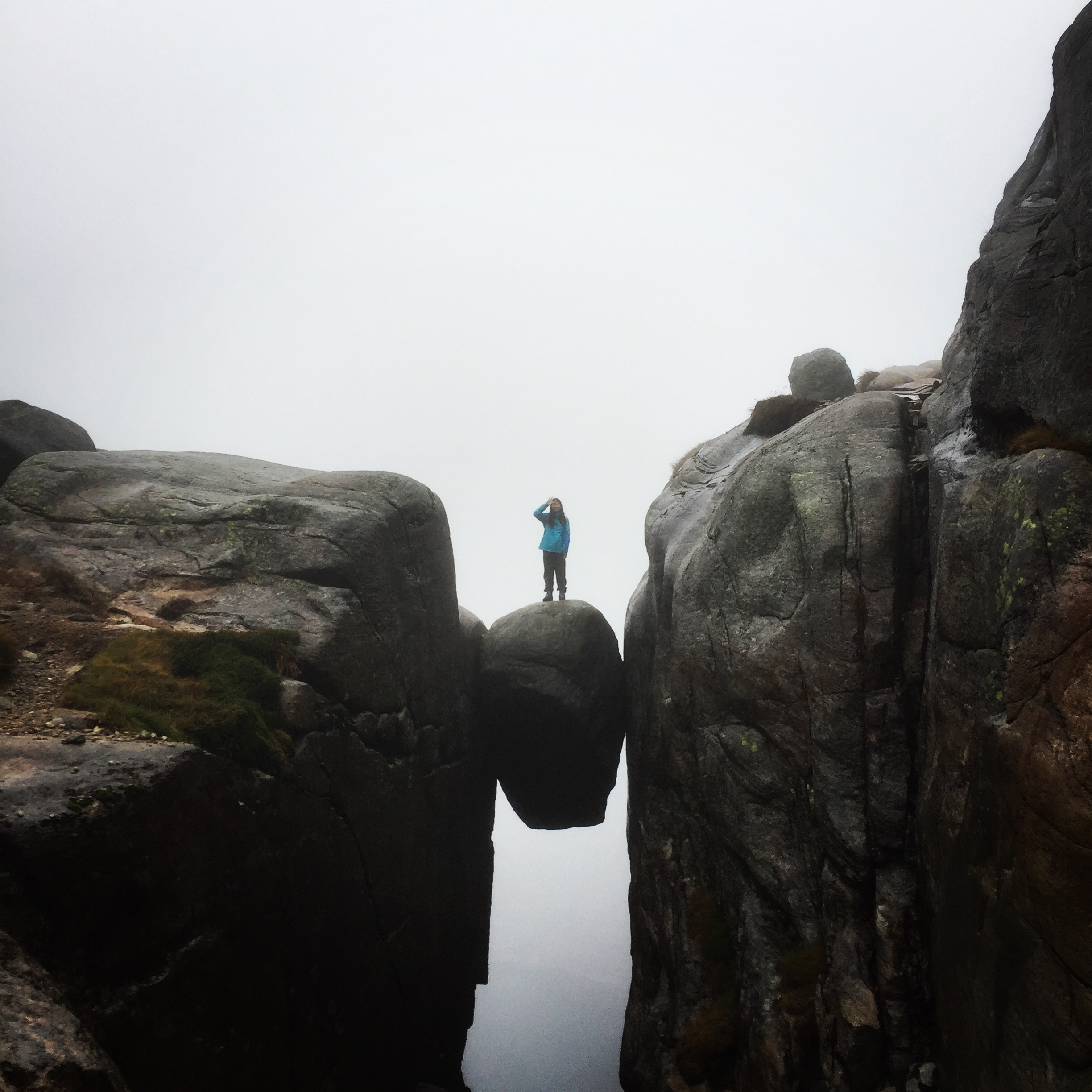 Person standing on the rock formation  Kjerag Bolt, about 700 meters above the fjord Lysefjorden