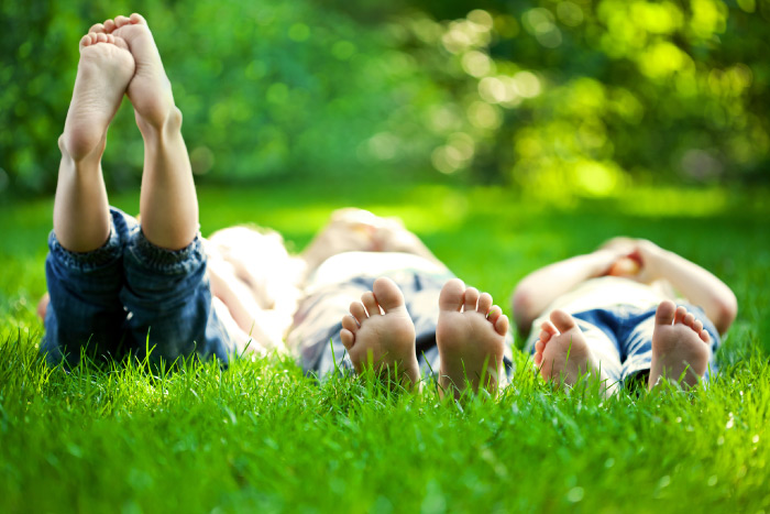 Children laying on the ground in a natural environment thinking about sustainability.