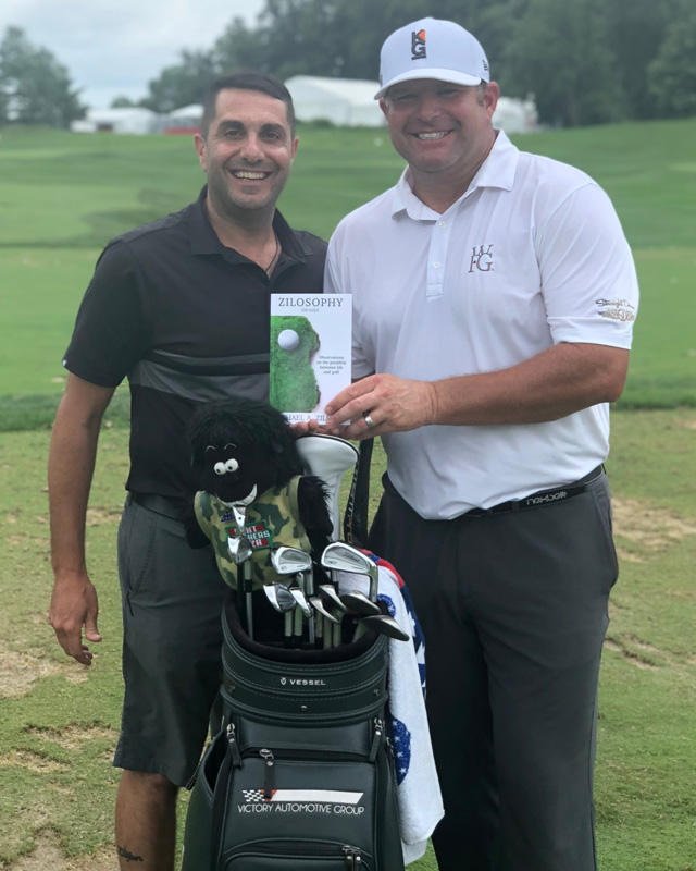 Golfers posing for picture with book and golf clubs