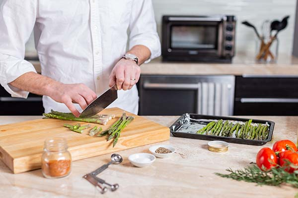 A man chopping asparagus and placing them on a Tovala sheet tray.