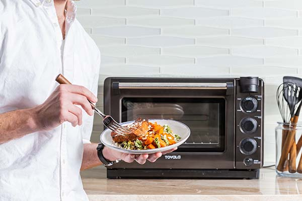 A man standing in front of a Tovala Oven holding a plated Tovala Meal.