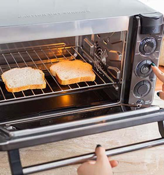 Two slices of bread inside a Tovala Oven and a person selecting a toast cycle.