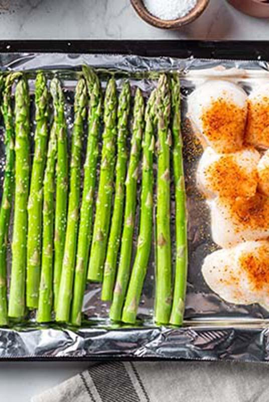 Asparagus and scallops on a sheet tray.