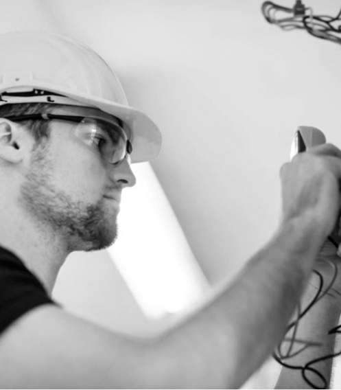 A photo of a guy doing electrical installation as part of  STO Property Maintenance services