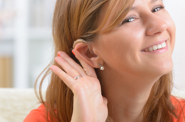 Young woman showing off her new behind the ear hearing aid.