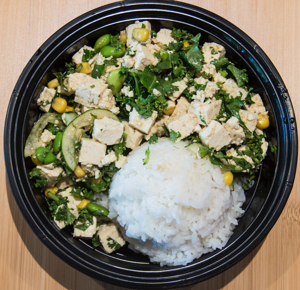 Overhead view of a bowl with a scoop of rice and fresh veggies