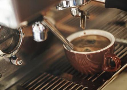 Sorso Coffee - espresso machine dripping espresso into a brown coffee cup