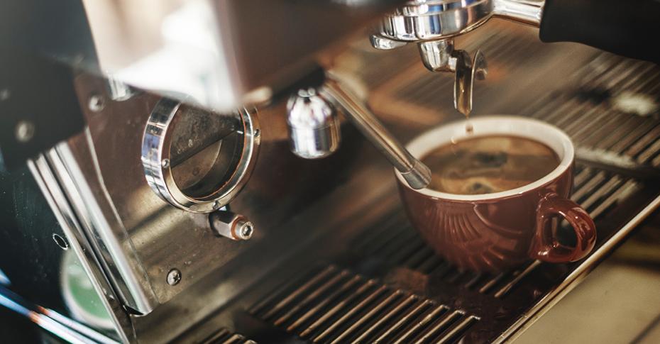 Espresso machine dripping espresso into brown coffee cup - sorso coffee