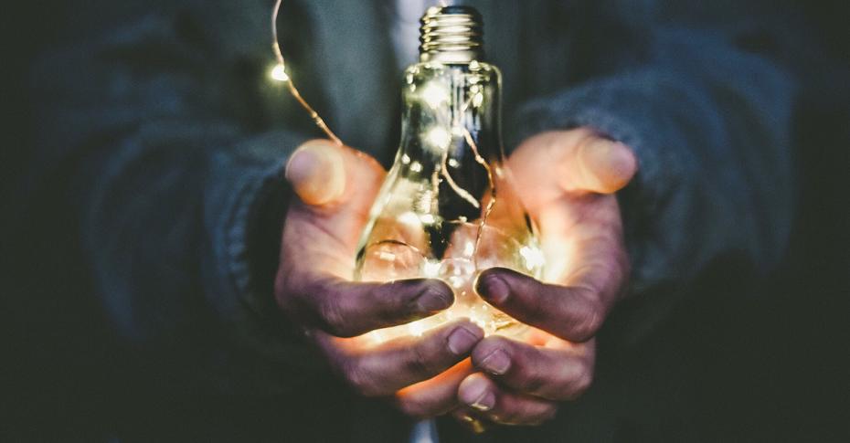 Man Holding illuminated idea lightbulb in handss