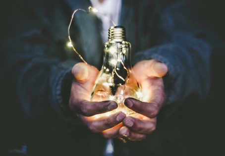 IdeaPros - person holding large glowing thought light bulb in hands