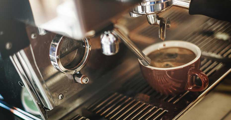 Stainless steel espresso machine dripping into brown espresso cup