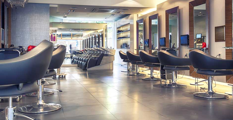 High end salon with a variety of styling chairs, mirrors and tvs on the wall