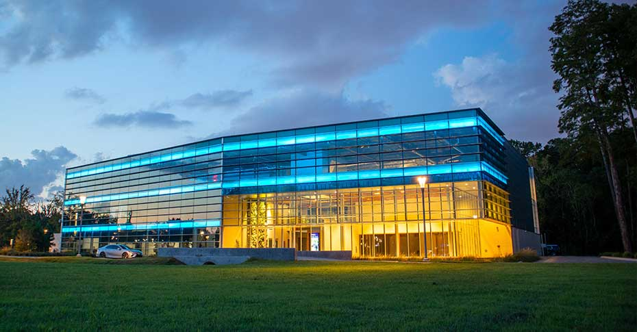 Modern glass building with blue neon lights and bright yellow interior lighting