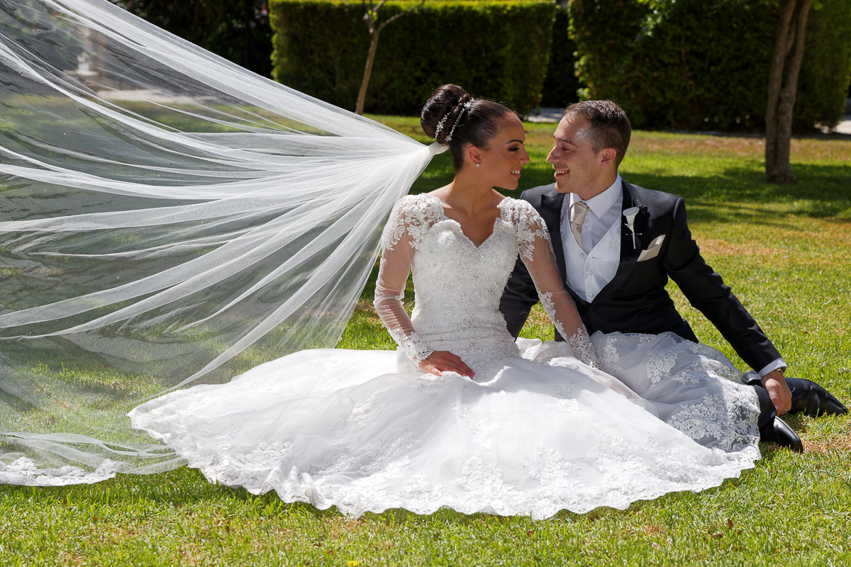 portrait of bride and groom sitting on the lawn outside the church