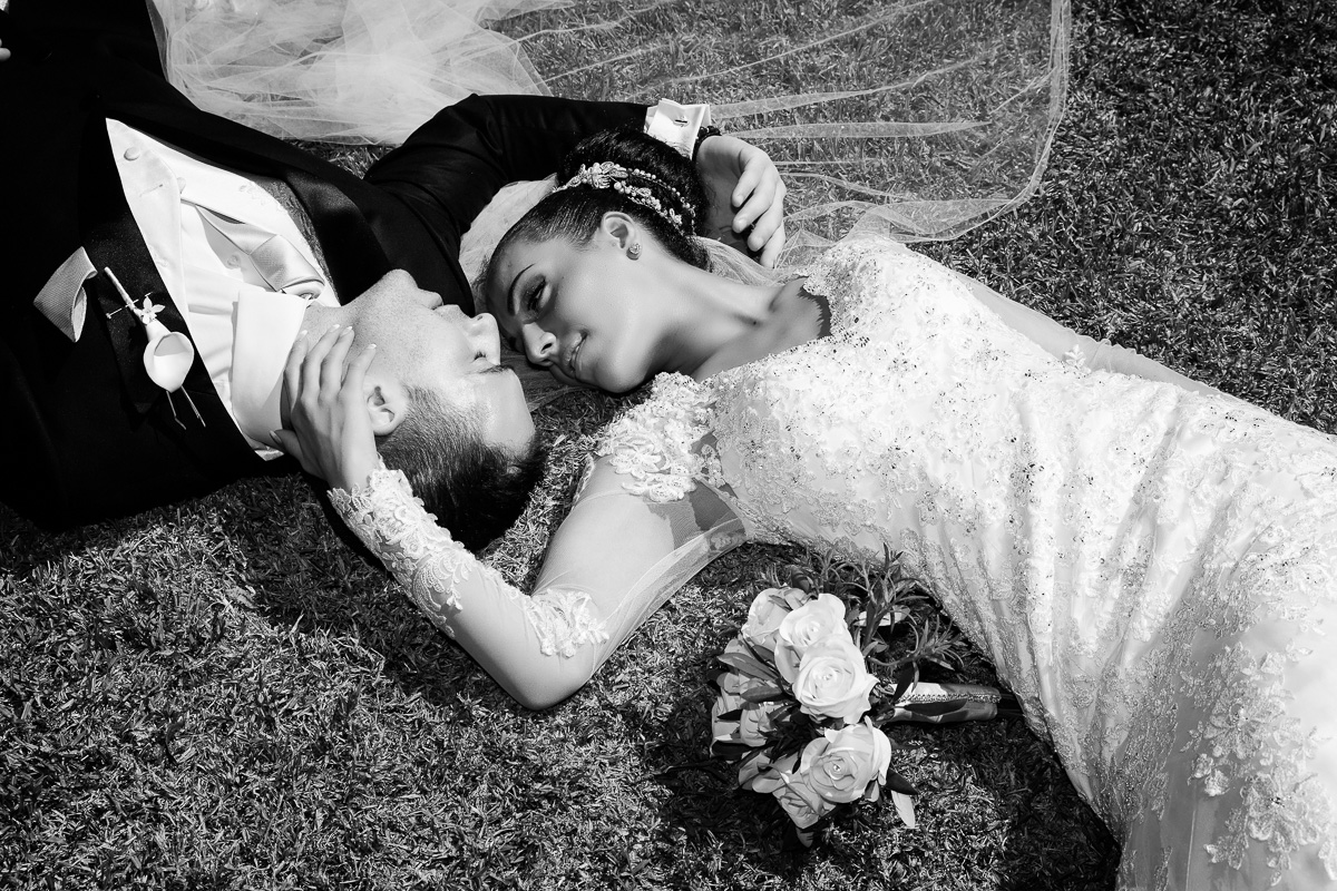 bride and groom looking at each other romantically while lawing on the lawn