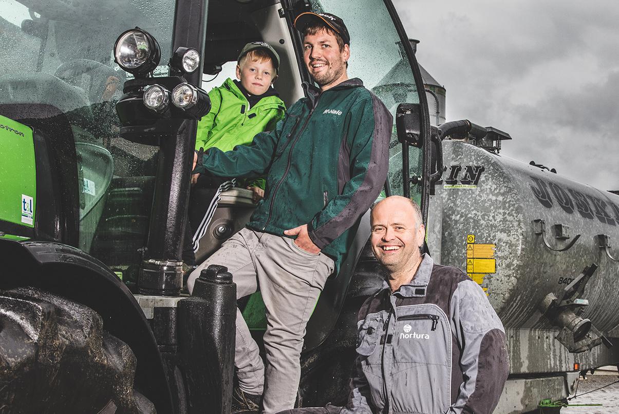 Bilde av bønder som står på ein traktor