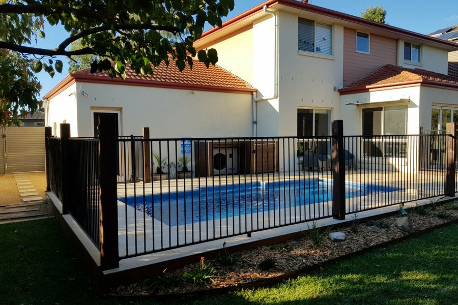 Himalayan Sandstone finish to the pool area, chucky timber posts and a traditional square top metal fence section.