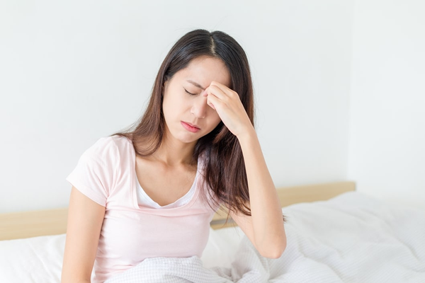 Young woman sitting on edge of bed, experiencing sinus pressure between her eyes.