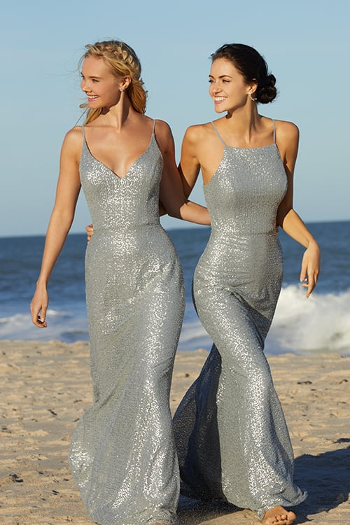 Two bridesmaids walking on a beach