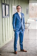 science fiction with cyberpunk elements author T. K. Young standing in a blue suit in front of olive green building smiling