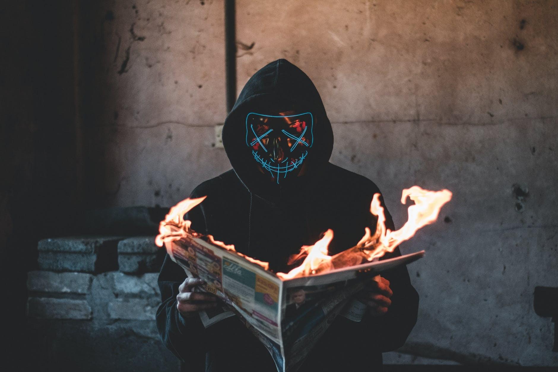 a cyberpunk burning a newspaper