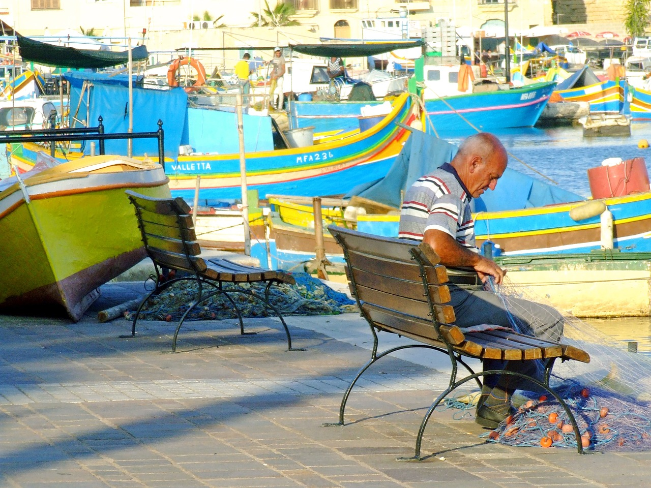 Rybář opravující síť v rybářské vesnici Marsaxlokk