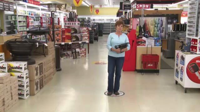 Wide-angle photo of a woman in the aisle of a retail store