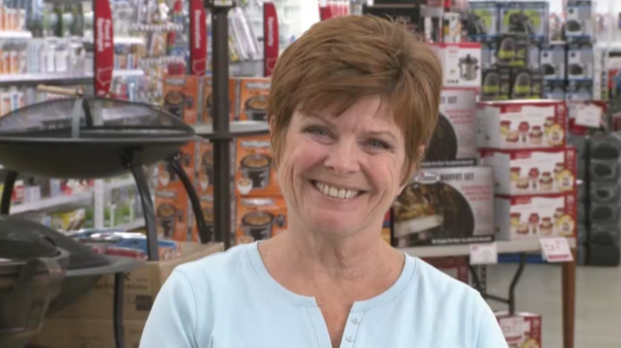 Close-up photo of a woman smiling in the aisle of a retail store