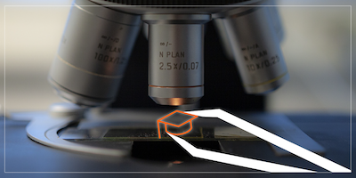Photo of a microscope with an illustrated graduation cap being placed on the tray using tweezers.