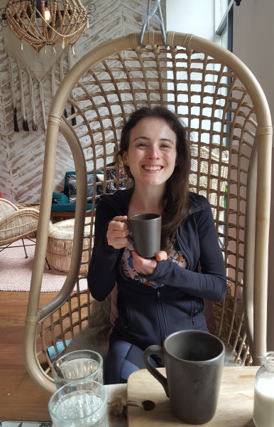 Ciara Kelly drinking tea on a bamboo chair with a big smile on her face