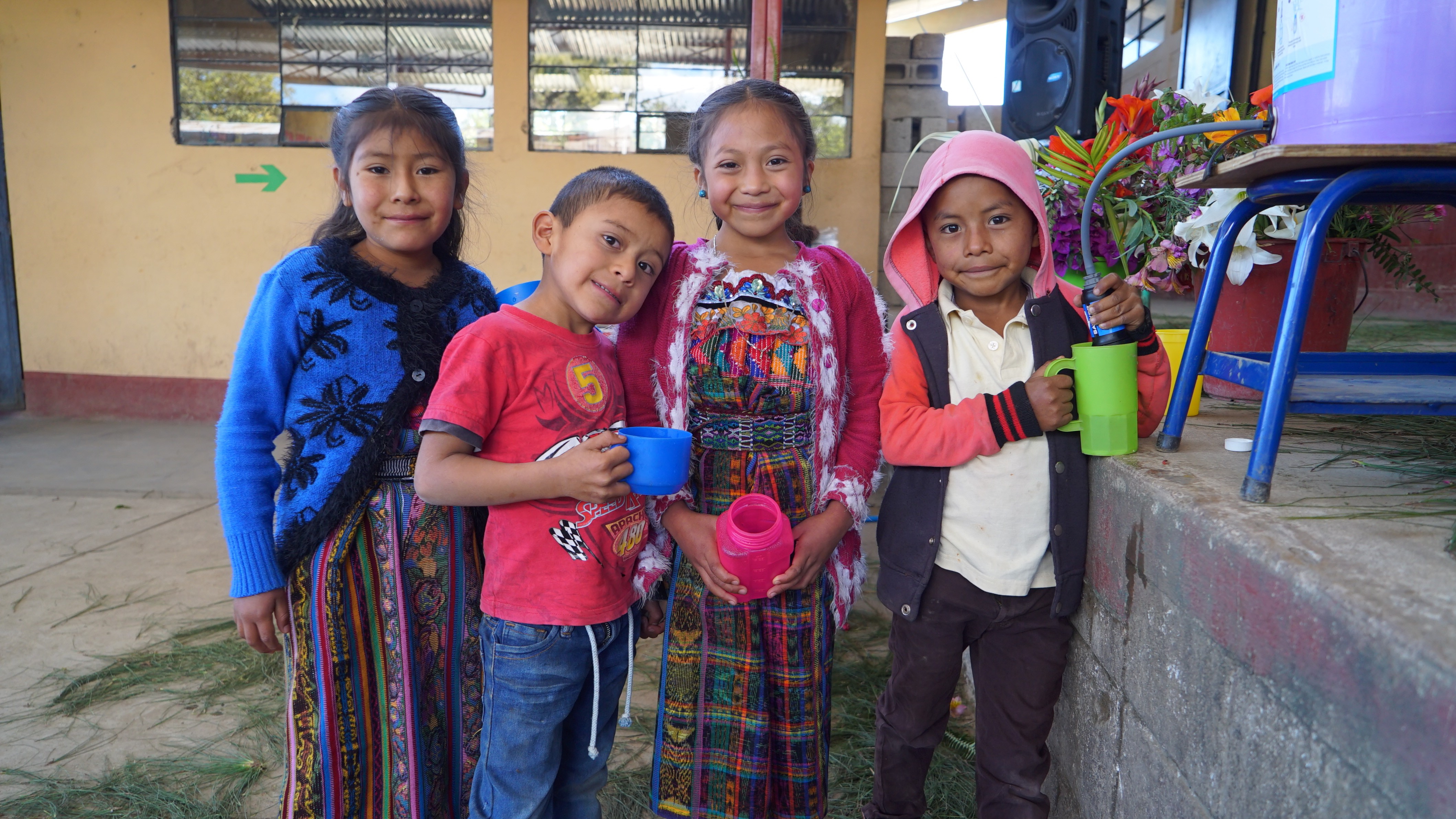 Guatemalan children holding cups of water next to a water filter