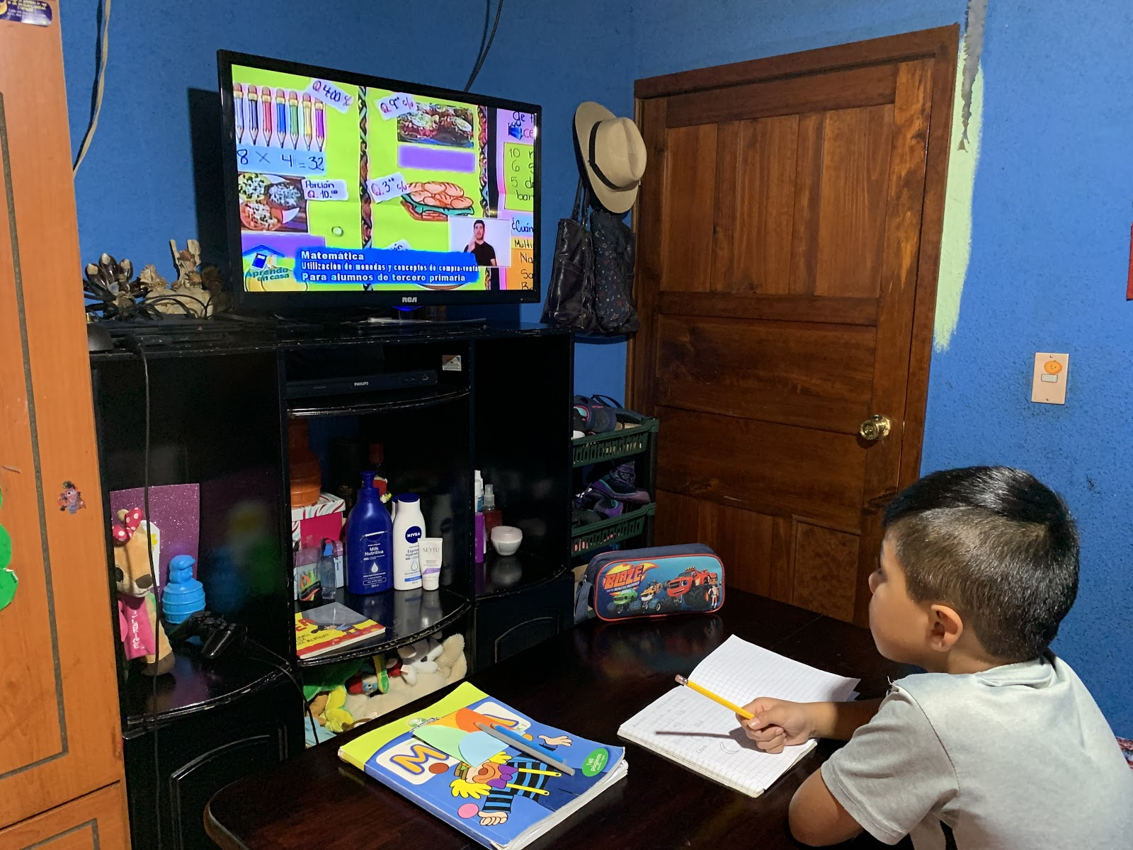Child doing homework and watching television